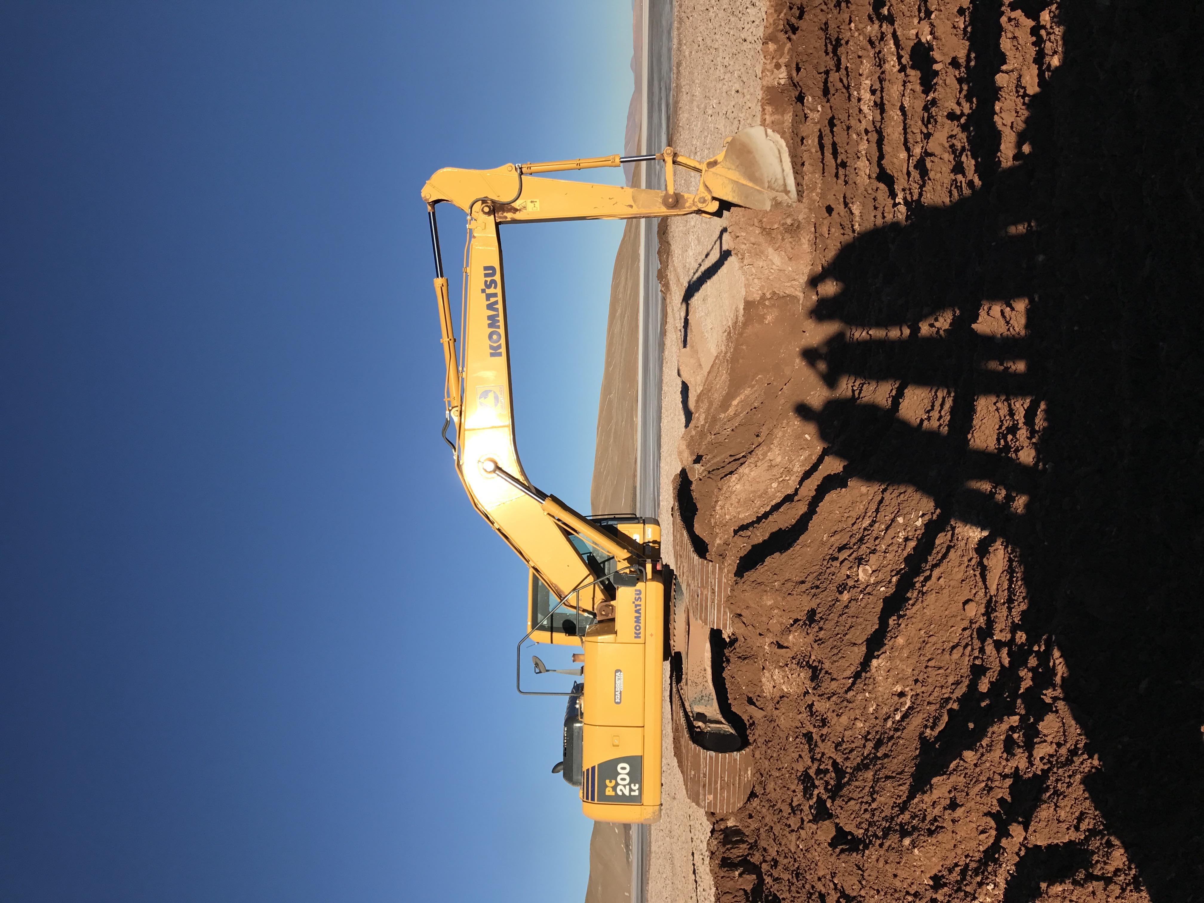 Foto excavadora con sobra de trabajadores